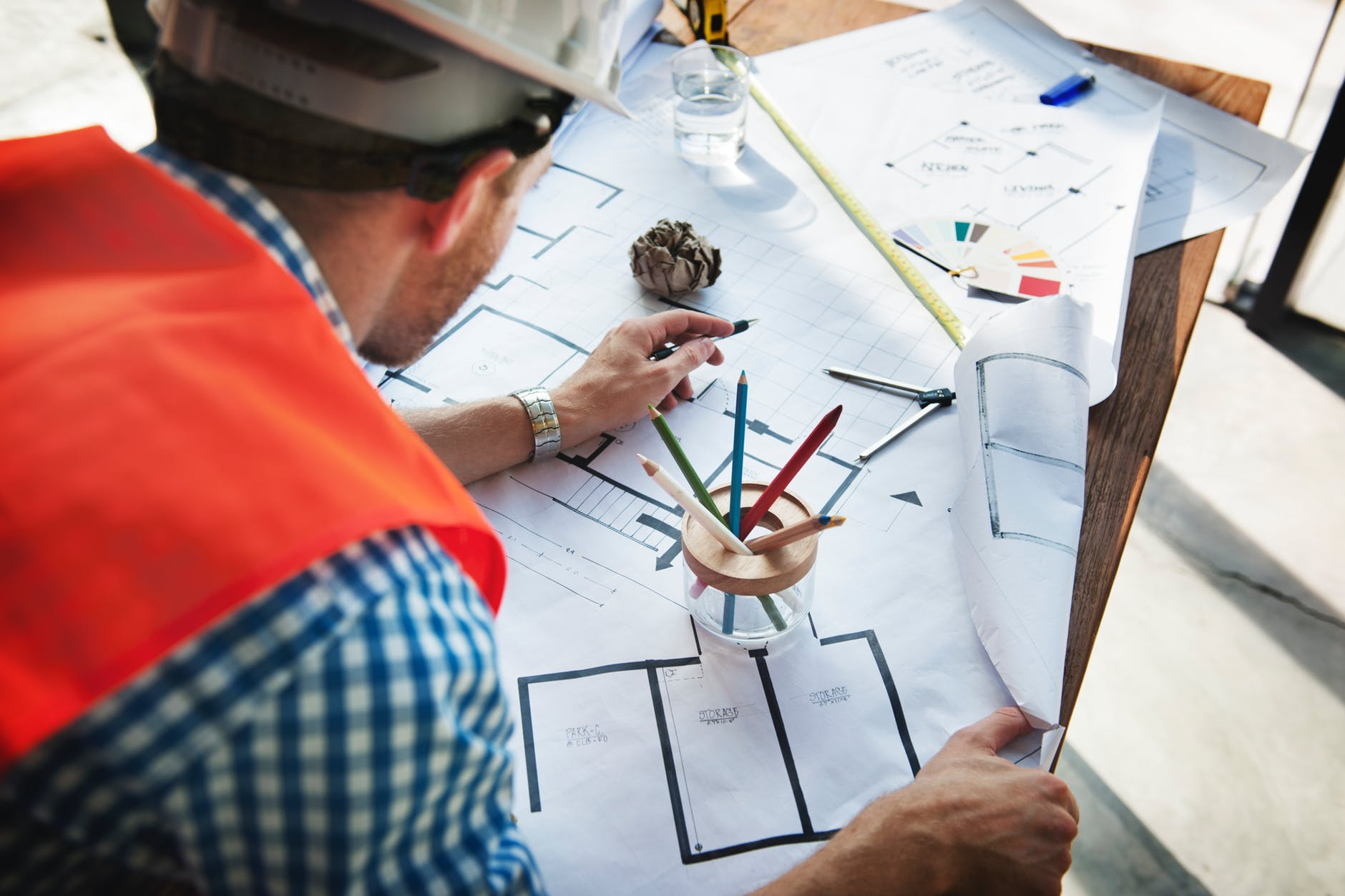man wearing white hard hat leaning on table with sketch plans